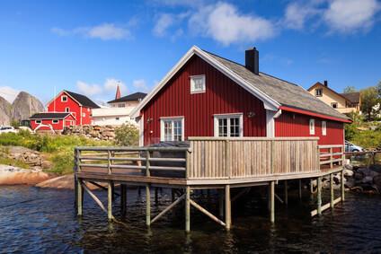 Une maison en bois rouge, situé a un lac