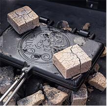 Lecker Brüsseler Waffeln aus dem Waffeleisen. Die aufgelegten Kohlebriketts geben die Hitze an die Gusseisenform ab.